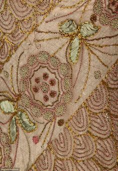 Detail of the embroidered blossoms and foliage in blue and pink metal beads. The blue applique silk is deteriorated.