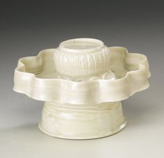 AN UNUSUAL WHITE-GLAZED FLUTED CUPSTAND FIVE DYNASTIES of circular section, supported on a wide splayed base, the tray with high fluted sides, enclosing the central bud-form pedestal with petal-grooved sides from a collar of emerging ruyi lappets, covered overall in a translucent ivory-colored glaze pooling to an olive-green along the base and foot Diameter 5 1/8  in., 13 cm                                                                            of circular...