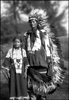 Unidentified Dakota Native Americans, pose near a large tree. Date between 1870 and 1890.