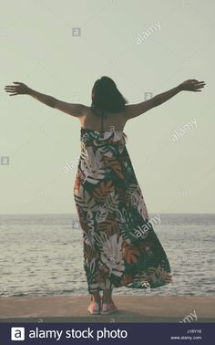 Rear view of a happy young woamn arms outstretched standing on the beach Stock Photo