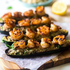 Cauliflower rice is mixed with vegetables, fresh lemon, stuffed into grilled zucchini and topped with shrimp. An easy, Paleo meal for under 200 calories!
