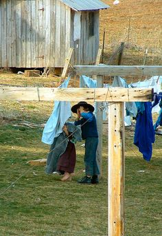 Amish kids playing in the clothesline...