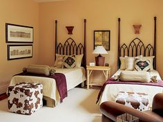 """Home on the Range ~ Based around the theme of """"cowboys and Indians,"""" the furniture and fabrics in this bedroom have a western feel. The palette of taupe and brown gets a shot of color with the addition of maroon throws folded at the end of each bed."""