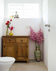 Piso de cimento queimado e móvel de madeira de demolição no banheiro do ateliê de Calu Fontes.