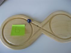 """Het """"lemniscaat""""-bord kan ook gebruikt worden ter ondersteuning en in""""slijten"""" van een letter of cijfer welke het kind moeilijk vindt. Plak een blaadje met een letter op één van de kanten van het bord. Laar de knikker """"rondgaan""""over de lemniscaatvorm. Als de knikker bij het papiertje met de letter is dan deze laten uitspreken."""