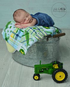 A new little boy who loves green tractors. Newborn photography. John Deere.