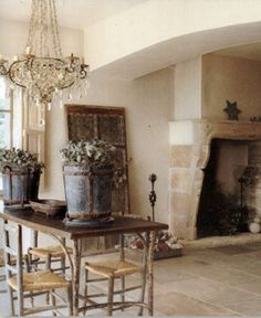 Casual elegance that is almost royal? What I love about this is the mixture of the heavy (the metal bins on table) with the lightness of the chandelier, and the weathered door against the wall with the weighty, masculine fireplace, but the colors are creamy and billowy. Works for me!!