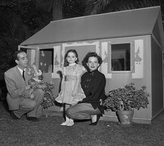 Vincente Minnelli and Judy Garland play with daughter Liza at her miniature house