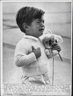 """CAPTION - """"PARTING GRIEVES HIM"""" - Weeping bitterly, John F. Kennedy, Jr., two-and-a-half year old son of President and Mrs. Kennedy walks across the ramp of Andrews Air Force base after his father left for a dam dedication in Arkansas.  The boy was sent back to the White House in the helicopter that flew him and his father to the air field.  His mother is vacationing in Greece.  --  October 3, 1963"""