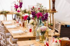 Pink and purple flowers are arranged in a natural style in bottles and jars for a rustic feel at this summer wedding by glass slipper weddings