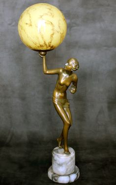 ART DECO spelter figure lamp, circa 1930, Germany - The dark gold gilded spelter figure mounted on a top hat alabaster base holding aloft an original glass globe - 61cm high - This is a beautiful art deco spelter lamp, with great style and lovely slim lines.