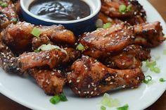 Asian Chicken Wings sprinkled with sesame seeds and served with hoisin sauce.