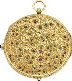 Ruby, Sapphire, Emerald, Lapis Lazuli, Gold Compact  The hinged compact, designed with a floral motif, features round-cut rubies, sapphires, and emeralds, enhanced by an oval-shaped lapis lazuli cabochon thumbpush, set in textured 18k yellow gold, topped off by a bail. The compact opens to reveal a mirror and powder compartment, lifted by a lapis lazuli cabochon tip. Gross weight 173.00 grams.  Dimensions: 3-3/4 inches x 3-1/8 inches