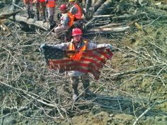 SSgt. Michael Cohan displays an American flag found in rubble of the Wa. mudslide - via Washington National Guard: