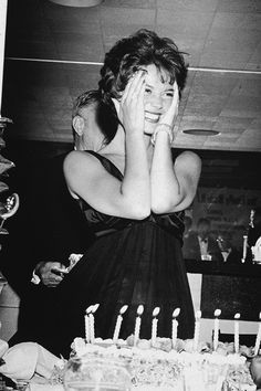 Happy Birthday ! Natalie Wood smiles and holds her hands to her face, standing behind her birthday cake during her surprise 21st birthday party, Romanoff's, Hollywood, photographed by Murray Garrett, 1959.