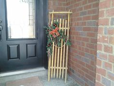 Tobacco sticks sled I made.  The decoration is 3 cut pieces of garland wired together with pine cones and Christmas balls hot glued to garland.