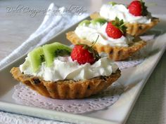 Barchette dolci ripiene con panna e frutta: golosi dolcetti composti da un guscio di biscotto con gocce di cioccolato, riempiti di frutta e panna montata..