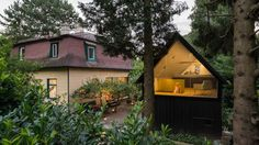This compact writer's cabin nestles behind a 1930s home in a small town outside of Vienna, its dark charms playing foil to the more traditional house beside it.
