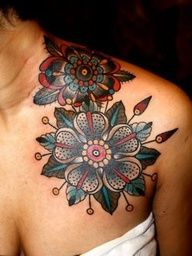 Two flowers tattoo around the shoulder and the neck.  A lovely alternative to something everyone has.