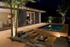 terrasse en bois composite avec piscine, bancs et coussins gris