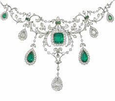 A belle époque emerald and diamond necklace, circa 1910  The foliate garlands of old brilliant and single-cut diamonds, highlighted with square-cut emeralds, suspending a fringe of graduated pear-shaped emeralds and diamonds, to a central step-cut emerald, each within an old brilliant and single-cut diamond surround, to a figaro-link backchain, millegrain-set throughout, diamonds approximately 4.40 carats total, length 41.0cm, fitted case by Wilson & Gill, 139 Regent St London W.