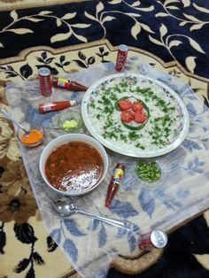 """Typical arabic """"Table"""". Plastic on the floor, food spread on plastic, cokes or pepsis and hot sauces fo sho."""