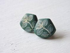 Ohrstecker in einem schönen, kräftigen dunkelgrün. In den grünen Polymer Clay wurde ein Blattadruck eingearbeitet und dieser wurde anschließend weiß & gold lackiert. Diese Ohrstecker sind...