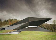 Conçue par Delugan Meissi Associated Architects, non loin de Vienne en Autriche, cette salle de concert et de théâtre est dès plus géométrique, sculpturale et semble avoir atterri en pleine nature. Assez impressionnant, tant par sa forme que par son noir pur et entier, cette structure permet d'abriter de gigantesques pièces dont les volumes sont à couper le souffle.