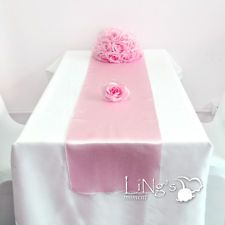 pink table runners with white tablecloths on 2.4 metre trestle tables. I will tie a little ribbon bow to gather the end of each runner. Maybe gold ribbon?