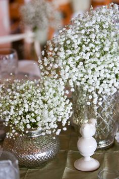 The Buttons' reception tables were topped with pintuck linen cloths, mercury glass vases, ceramic birds, and fluffy baby's breath poufs.