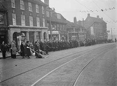Royal British Legion flags being lowered in respect at the Eltham Armistice Memorial Service . 1937