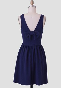 Adorned with a darling bow at the back, this deep navy dress is perfected with a textured, stretchy  fabric, a V-cut neckline, and a gently pleated fit-and-flare silhouette for added feminine fla...