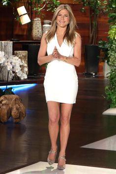 Bei Jennifer Aniston strahlen ihr Lächeln und ihr Saint Laurent Kleid um die Wette. Der dezente Goldschmuck und die Pumps in Schlangenoptik passen gut zum schlichten Weiß.