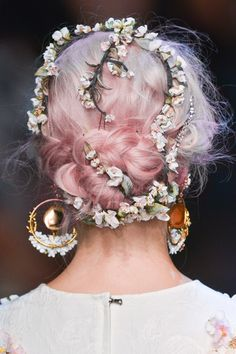 Pink hair with little flower garland wreathed through braided knot.