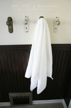 Use thrifted door knobs in place of towel hooks. Could also use to hang coats, handbags, etc.