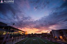 The sun sets over the University of Arizona campus, reflecting off the new Lowell-Stevens Football Facility at Arizona Stadium.