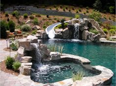 Backyard resort with lagoon style pool, waterslide, rock waterfall, boulder accents, and spa. Dolphin Waterslides; Creative Ponds http://www.poolspaoutdoor.com/blog/entryid/207/7-pool-spa-designs-for-2014.aspx