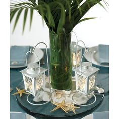 Miniature lanterns with hangers, in white, add a warm glow to a beach or nautical theme wedding. Combine with sea shells, sand and starfish for a centerpiece that brings the beach inside.Materialsmetal and glassSold in sets of 2.Chair dimensions: 6 1/2