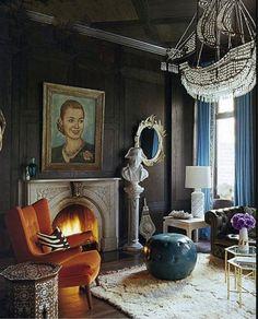 Blues curtains, dark walls, orange sofas and white wood furniture