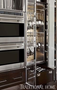 """A glass-front cabinet for hanging pots and pans with a drawer for lids is built in next to the wall ovens, keeping cookware organized and accessible but without clutter. """"Because the kitchen is so open to other living spaces, the homeowners didn't want to see things on the countertops,"""" De Giulio says."""