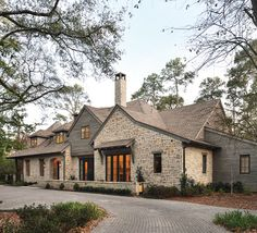 he exterior of the home was a collaboration be­tween the owners and designer. The subtle gray wash of the siding complements the stone from Alamo Stone. Hundreds of trees provide natural beauty as well as privacy for the homeowners. Stone Exterior Houses, Stone Houses, House Exteriors, Home Room Design, House Design, Cottage Design, House And Home Magazine, House Goals, Texas Hill Country