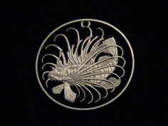 This crazy coin was hand cut from a 50 cent coin from Singapore.   It features a lion fish, the most feline-inspired fish of all time (next to the catfish).  It was a crazy task to cut, and I will not cut another in this life.