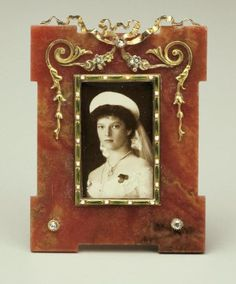 Fabergé rhodonite frame, c. 1900, with photograph of Grand Duchess Olga, daughter of Tsar Nicholas II. Aperture with a border of gold, green enamel and pearl dots. At top of frame is a lover's knot in gold with a tiny diamond. From this hangs swags and loops in gold and silver flowers. At two lower corners are two tiny diamonds set in gold. Hillwood, Marjorie Merriweather Post.