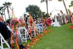 Birght, tropical style aisle markers with flowing ribbons in orange and fuchsia.  Designed by Bella Flora 30a