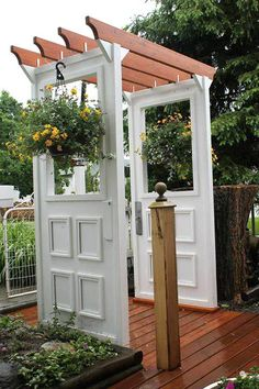 Use old doors to add vertical interest to your garden. This door arbor holds hanging baksets of flowers.