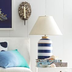 This bold, bright, hand-painted lamp is a modern take on the classic blue and white stripe, updated with golden bands and a complementary linen shade. The iron base is modeled from antique British Indian tea caddies, breathing new life into an old tradition. This showstopper looks great on simple, plain surfaces like an oak side table. Pro tip: Extending your pinkie when drinking tea is a sign of royalty.