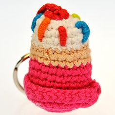 Hand crocheted Cupcake Keyring. This keyring is based on our Pebble range of baby rattles from Hathay Bunano in Bangladesh. These keyrings are utterly gorgeous; handmade from cotton (and machine washable!), they will look after your keys and provide you with a smile every time you look at them. All measurements are approximate.  Diameter : 43mm Height : 55mm Length of Cord : 38mm Keyring Diameter : 30mm