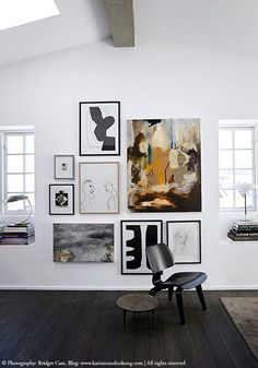 Art on the walls & black floorboards.  Monocrome artwork alongside colour painting, if a cushion was needed why not introduce a digital geometric pattern?  Olive Living.