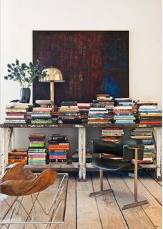 Leather chair, glass table, salvaged shelf, piles of books, vase, chrysanthemums, gold lamp, ivory walls, abstract canvas, natural light.