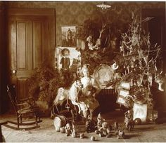 Antique Photo, c1900, of a child standing by the Christmas tree surrounded by rocking horse, Buster Brown Game, & Schoenhut Circus toys.
